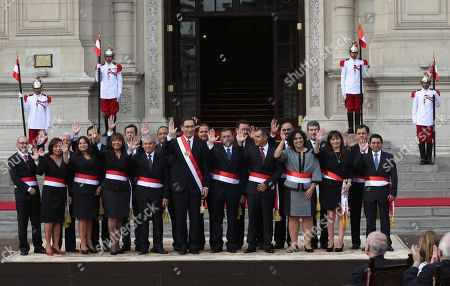 Peru's President Martin Vizcarra, center, waves alongside his new cabinet during their swearing-in ceremony at the government palace in Lima, Peru, . Vizcarra was sworn-in to office in March, taking over from his predecessor Pedro Pablo Kuczynski who resigned over corruption allegations