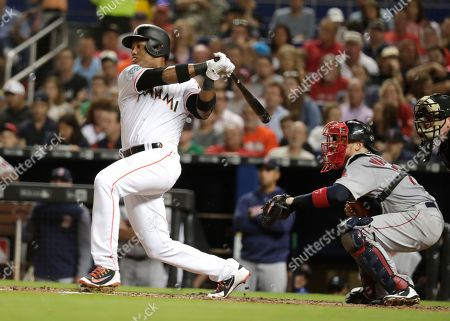 Christian Vazquez, Starlin Castro. Miami Marlins' Starlin Castro, left, hits a single in the third inning of a baseball game against the Boston Red Sox, in Miami. At right is Boston Red Sox catcher Christian Vazquez