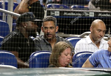Stock Image of Derek Jeter, David Ortiz, Jorge Posada. Derek Jeter, part owner of the Miami Marlins, right, sits with former designated hitter of the Boston Red Sox David Ortiz, left, and former catcher of the New York Yankees Jorge Posada, center, during a baseball game between the Miami Marlins and Boston Red Sox, in Miami