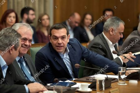 Stock Photo of Alexis Tsipras, Yannis Dragasakis, Panos Kammenos. Greek Prime Minister Alexis Tsipras, centre, talks with Economy and Development Minister Yannis Dragasakis, second left, and Defense Minister Panos Kammenos during a cabinet meeting in Athens, Tuesday, April, 2018. Tsipras on Tuesday renewed a call on neighbor Turkey to release two Greek soldiers arrested on a border patrol last month