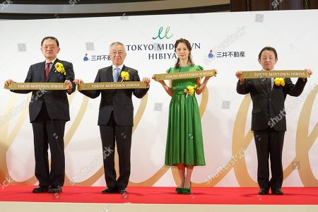 Japanese actress Aoi Miyazaki (C-R) alongside other guests pose for the cameras during the opening ceremony for Tokyo Midtown Hibiya shopping mall