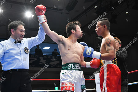 Akira Yaegashi of Japan has his arm raised by referee Kazutoshi Yoshida as he talks his opponent Frans Damur Palue of Indonesia after winning the 10R super flyweight bout