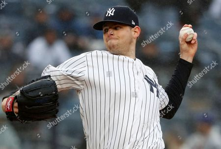 New York Yankees starting pitcher Jordan Montgomery winds up during the first inning of an opening day baseball game against the Tampa Bay Rays at Yankee Stadium in New York