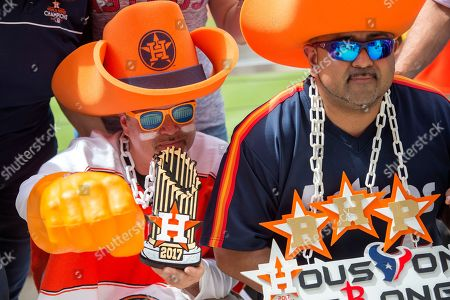 David Arriasola, left, and Carlos Campos, Astros fans who call themselves the Big Hat Posse, pose for a photo before a baseball game between the Texas Rangers and the Houston Astros, in Arlington, Texas. Houston won 9-3