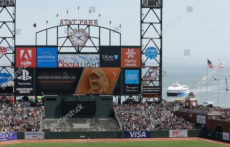 Stock Picture of A tribute to former San Francisco Mayor Ed Lee is seen on the centerfield scoreboard before the start of an opening day baseball game between the San Francisco Giants and the Seattle Mariners, in San Francisco. Lee died in December 2017