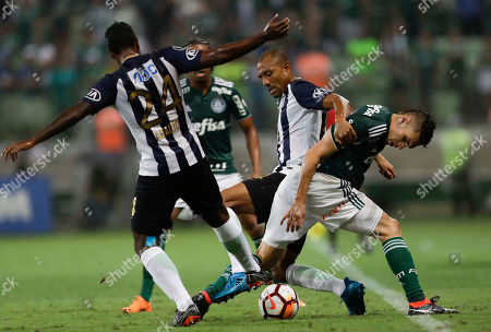 Moises of Brazil's Palmeiras, right, fights for the ball with Miguel Gianpierre Araujo, left, and Luis Alberto Ramirez Lucay of Peru's Alianza, center, during a Copa Libertadores soccer match in Sao Paulo, Brazil