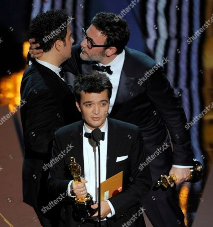 """Best director winner Michel Hazanavicius, right, embraces Ludovic Bource, winner of best original score as producer Thomas Langmann, center, speaks after accepting the Oscar for best picture for """"The Artist"""" during the 84th Academy Awards, in the Hollywood section of Los Angeles. The film won a total of five Oscars"""