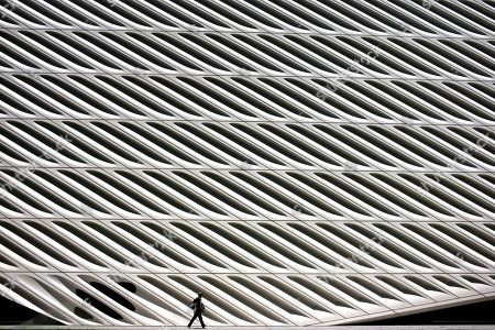 A man is dwarfed as he walks past The Broad museum, in downtown Los Angeles. The contemporary art museum was founded by philanthropist Eli Broad in 2015