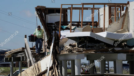 Shane Johnson removes items from a family home destroyed in the wake of Harvey, in Rockport, Texas