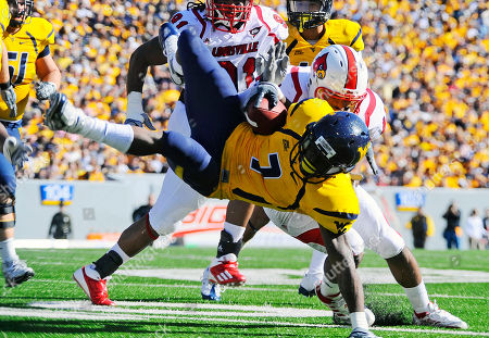 West Virginia's Noel Devine is brought down during the second quarter of a NCAA Football game against Louisville, in Morgantown, W.Va