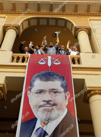 Egyptian campaign officials of the Muslim Brotherhood's candidate, Mohammed Morsi, celebrate over a giant poster of him at his campaign headquarters in Cairo, Egypt, . Mohammed Morsi was declared Egypt's first Islamist president on Sunday after the freest elections in the country's history, narrowly defeating Hosni Mubarak's last Prime Minister Ahmed Shafiq in a race that raised political tensions in Egypt to a fever pitch