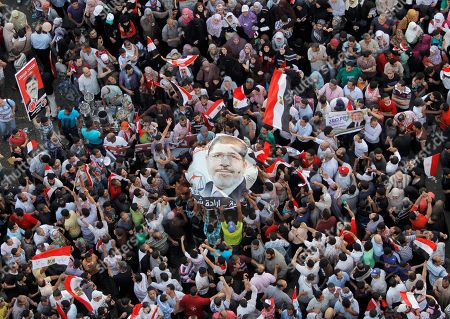 Egyptians carry a poster showing newly-elect President Mohammed Morsi, in Tahrir Square, Cairo, Egypt, . Mohammed Morsi was declared Egypt's first Islamist president on Sunday after the freest elections in the country's history, narrowly defeating Hosni Mubarak's last Prime Minister Ahmed Shafiq in a race that raised political tensions in Egypt to a fever pitch