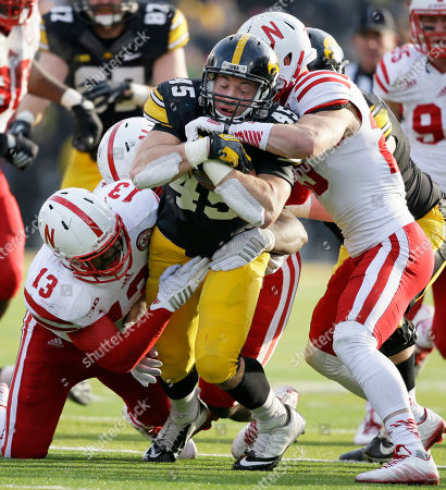Mark Weisman, Zaire Anderson, Nate Gerry. Iowa running back Mark Weisman, center, is tackled by Nebraska defenders Zaire Anderson (13) and Nate Gerry, right, during overtime in an NCAA college football game, in Iowa City, Iowa. Nebraska won 37-34 in overtime