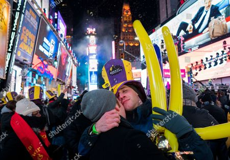 Patrick Graver, right, of New York, embraces Justin Kelly, also of New York, in Times Square, as they take part in a New Year's celebration in New York