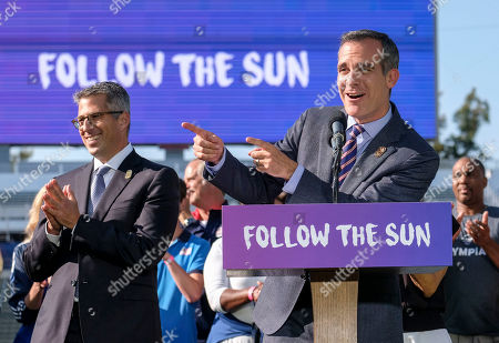 LA Olympic Committee leader Casey Wasserman, left, applauds as Los Angeles Mayor Eric Garcetti speaks during a press conference to make an announcement for the city to host the Olympic Games and Paralympic Games 2028, at Stubhub Center in Carson, outside of Los Angeles, Calif