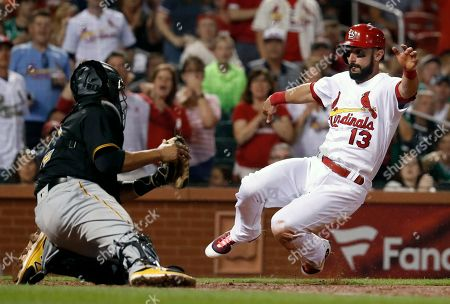 St. Louis Cardinals' Matt Carpenter (13) scores past Pittsburgh Pirates catcher Elias Diaz during the fifth inning of a baseball game, in St. Louis