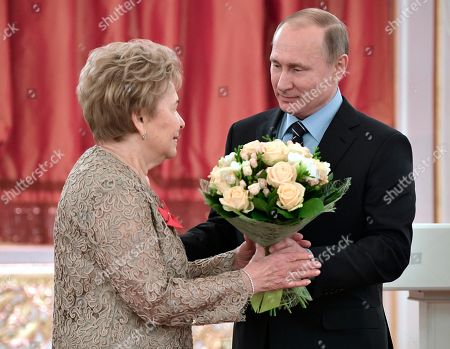 Russian President Vladimir Putin gives flowers to Naina Yeltsin, widow of the first Russian President Boris Yeltsin, at a reception marking her 85th birthday in the Kremlin in Moscow, Russia