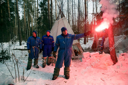 Stock Photo of Andrew J. Feustel, Oleg Artemyev, Sergej Prokopyev. NASA astronaut Andrew J. Feustel holds a flare as Russian Cosmonauts Oleg Artemyev, left, and Sergej Prokopyev stand near the hut which they built during a three-day winter training in a forest at Russian Space Training Center in Star City, outside Moscow, Russia, . The three are being trained for a future mission to the International Space Station