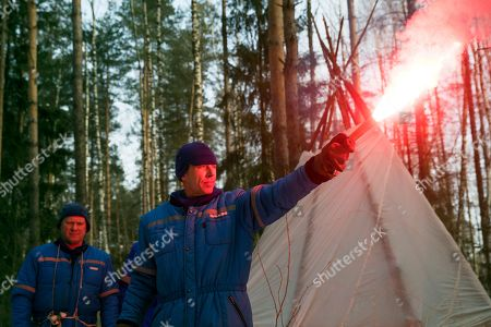 Andrew J. Feustel, Oleg Artemyev. NASA astronaut Andrew J. Feustel holds a flare as Russian Cosmonaut Oleg Artemyev, left, stands near the hut which they built during a three-day winter training in a forest at Russian Space Training Center in Star City, outside Moscow, Russia, . The three are being trained for a future mission to the International Space Station