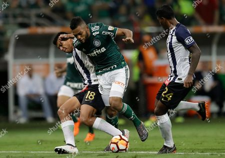 Miguel Borja of Brazil's Palmeiras, center, fights for the ball with Paulo Rinaldo Cruzado, left, and Miguel Gianpierre Araujo, of Peru's Alianza Lima, right, during a Copa Libertadores soccer match in Sao Paulo, Brazil