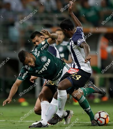 Miguel Borja of Brazil's Palmeiras, center, fights for the ball with Paulo Rinaldo Cruzado, behind, and Miguel Gianpierre Araujo of Peru's Alianza Lima, front right, during a Copa Libertadores soccer match in Sao Paulo, Brazil