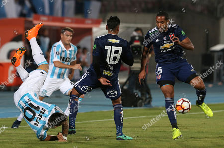 Lautaro Martinez of Argentina's Racing, left, falls as he fights for the ball with Gonzalo Jara of Chile's Universidad of Chile, center, as Chile's Jean Beausejour controls the ball during a Copa Libertadores soccer match in Santiago, Chile