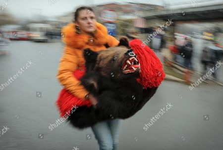 A woman carries a dancer's costume made of a bear's fur before a parade of new year's traditions in Comanesti, northern Romania, . The tradition, originating in pre-Christian times, when dancers wearing colored costumes or animal furs, went from house to house in villages singing and dancing to ward off evil, has moved to Romania's cities, where dancers travel to perform the ritual for money.(AP Photo/Vadim Ghirda