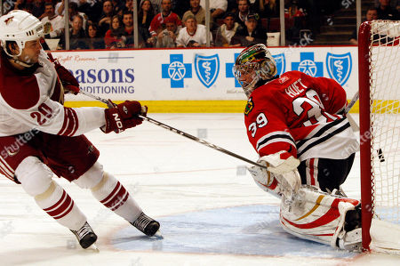 Robert Lang, Cristobal Huet. Phoenix Coyotes' Robert Lang, left, scores against Chicago Blackhawks goalie Cristobal Huet of France, during a shootout of an NHL hockey game in Chicago, . The Coyotes won 2-1