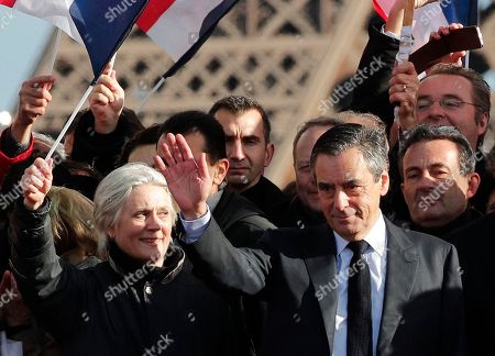 """Conservative presidential candidate Francois Fillon and his wife Penelope wave during a rally in Paris, . French conservative presidential candidate Francois Fillon is urging his supporters not to """"give up the fight"""" for the presidency despite corruption allegations dogging him"""