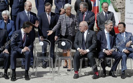 Canadian Finance Minister William Morneau, front row left, French Finance Minister Michel Sapin, front row third from right, and International Monetary Fund Managing Director Christine Lagarde, standing at center, look at the empty chairs of the Italian delegation as they wait with other participants for their family photo to be taken at the Norman-Swabian Castle, venue of the G7 of finance ministers, in Bari, southern Italy