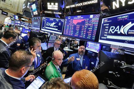 Specialist Peter Giacchi, background center, handles the close of trading of Reynolds American on the floor of the New York Stock Exchange