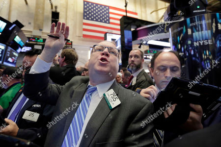 Trader Daniel Ryan works on the floor of the New York Stock Exchange, . Stock indexes are barely budging in early trading on Wall Street as investors look over a large batch of earnings reports from U.S. companies