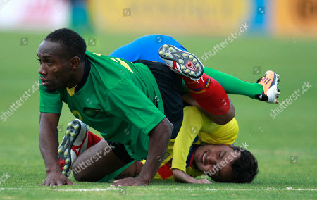 Jamaica's Richard Edwards left and Ecuador's Ivan Kaviedes get tangled on the pitch during a friendly soccer match in Quito, Ecuador, . Ecuador thrashed Jamaica 5-2