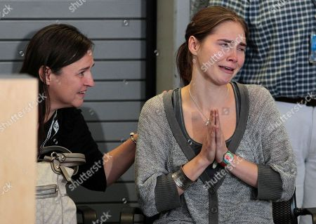 Amanda Knox motions to cheering supporters as her mother, Edda Mellas, looks on at a news conference shortly after her arrival at Seattle-Tacoma International Airport, in Seattle. It's been four years since the University of Washington student left for the study abroad program in Perugia and landed in prison. The group Friends of Amanda Knox and others have been awaiting her return since an Italian appeals court on Monday overturned her conviction of sexually assaulting and killing her British roommate, Meredith Kercher