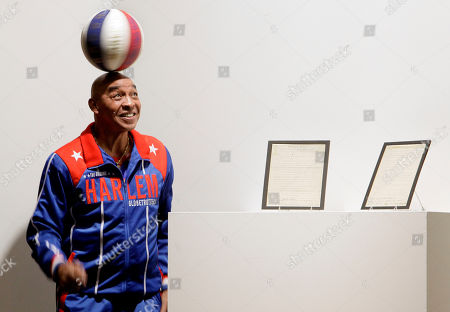 Stock Image of Former Harlem Globetrotters basketball player Curly Neal spins a ball on his head prior to the bidding for the Naismith Rules, the original rules for basketball, framed at right, at Sotheby's in New York