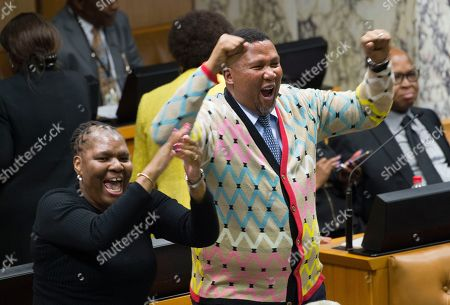 Mandla Mandela, centre, grandson of the late Nelson Mandela, jubilates in parliament, in Cape Town, South Africa after President Jacob Zuma again survived a no-confidence vote in parliament. This was the most serious attempt yet to unseat Zuma after months of growing anger over alleged corruption and a sinking economy