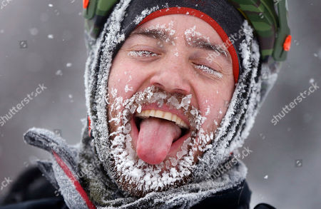 Stock Photo of Cyclist David Cassidy of Bangor, Maine, enjoys the moment after crossing the finish line in an 18-mile bike race at the Fat Tire Festival at the Sugarloaf ski resort, in Carrabassett Valley, Maine. Riders had to endure heavy snowfall and 2 degree F temperatures as parts of New England get hit with another winter storm