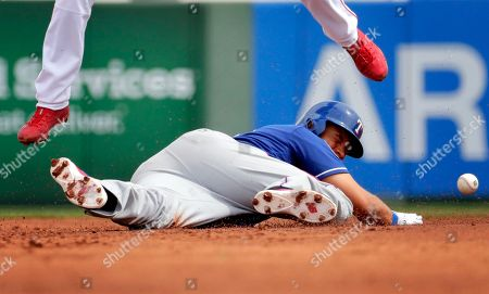 Texas Rangers' James Loney is hit by the throw diving back to second on a pick-off attempt as Los Angeles Angels' Andrelton Simmons leaps out of the way during the first inning of a spring training baseball game, in Tempe, Ariz