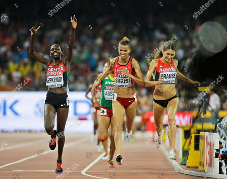 Kenya's Hyvin Kiyeng Jepkemoi, left, celebrates after winning the women's 3000m steeplechase final at the World Athletics Championships at the Bird's Nest stadium in Beijing, . Tunisia's Habiba Ghribi, center, finished second and Germany's Gesa Felicitas Krause, right, finished third