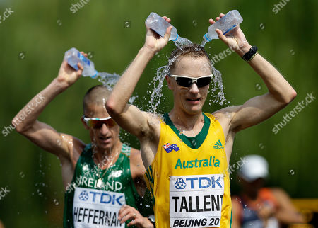 Australia's Jared Tallent, right, and Ireland's Robert Heffernan douse themselves with water during the men's 50k race walk at the World Athletics Championships outside the Bird's Nest stadium in Beijing