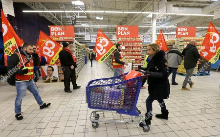 A woman pushes her trolley as employees of French retail giant Carrefour Group demonstrate against job cuts with union flags inside a Carrefour hypermarket, in Aix-en-Provence, southern France, . Carrefour CEO Alexandre Bompard announced last month cost savings of 2 billion euros (2.44 billion US dollars) by 2020. CGT union stands for General Working Confederation