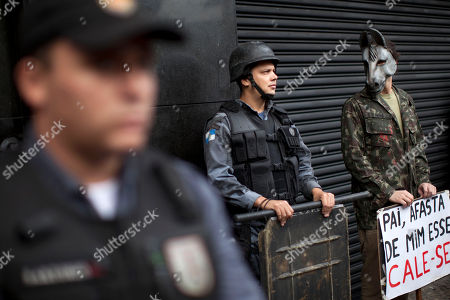 """An activist wearing a donkey mask stands next to police as they stand guard outside a military club during a protest in downtown Rio de Janeiro, Brazil, . A club of retired military officers held its annual celebration of Brazil's 1964 military coup as usual, but faced protestors as members arrived for the event. Unlike its Latin American neighbors, Brazil never had a formal investigation into its 20-year dictatorship. The sign reads in Portuguese """" Father keep that one away…shut-up,"""" a play on words from a song by famous singer Chico Buarque which was censored during the dictatorship"""