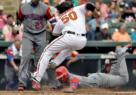 Jonathan Vallar, Zach Stewart. Baltimore Orioles pitcher Zach Stewart (50) goes airborne as he attempts to tag out Dominican Republic infielder Jonathan Villar (5) at home plate during the sixth inning of an exhibition baseball game, in Sarasota, Fla. Villar scored on a wild pitch by Stewart