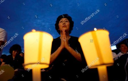 South Korean woman prays during a candle light vigil for the late former South Korean President Kim Dae-jung at Seoul Plaza in Seoul, South Korea, . South Korea said Saturday it is considering a request by visiting North Korean officials to meet President Lee Myung-bak, amid reports they were carrying a message from the communist country's leader