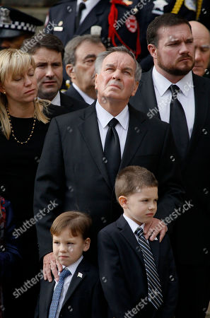 Former Chicago Mayor Richard M. Daley, surrounded by family, looks to the sky as the casket of former first lady Maggie Daley arrives at Old St. Patrick's Catholic Church in Chicago before her funeral service Monday, Nov., 28, 2011, Mrs. Daley died Nov. 24 after a long battle with cancer