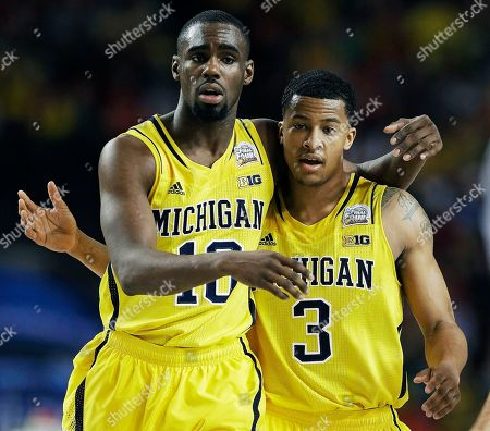 Michigan's Trey Burke, right, and teammate Tim Hardaway Jr. walk down the court during the second half of their NCAA Final Four tournament college basketball semifinal game against Syracuse, in Atlanta. Michigan won 61-56