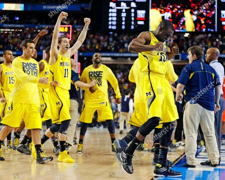 Michigan players including Tim Hardaway Jr., right, and Nik Stauskas (11) celebrate after defeating Syracuse in their NCAA Final Four tournament college basketball semifinal game, in Atlanta. Michigan won 61-56