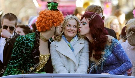 """Actress Amy Poehler, center, is kissed by Jason Hellerstein, left, and Sam Clark, who are dressed in drag, as she rides in a convertible through Harvard Square in Cambridge, Mass., . Poehler was honored as """"Woman of the Year"""" by the Hasty Pudding Theatricals at Harvard University"""