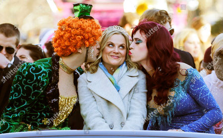 """Stock Photo of Actress Amy Poehler, center, is kissed by Jason Hellerstein, left, and Sam Clark, who are dressed in drag, as she rides in a convertible through Harvard Square in Cambridge, Mass., . Poehler was honored as """"Woman of the Year"""" by the Hasty Pudding Theatricals at Harvard University"""