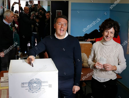 Italian Premier Matteo Renzi is flanked by his wife Agnese as he casts his ballot at a polling station in Pontassieve, Italy, . Italians are voting in a referendum on constitutional reforms that is being closely watched abroad to see if Italy is the next country to reject the political status quo. Premier Matteo Renzi has said he would resign if the reforms are rejected in Sunday's vote, and opposition politicians have vowed to press for a new government if voters reject the proposed constitutional changes